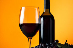 A picture of a wine glass, wine bottle and purple grapes.